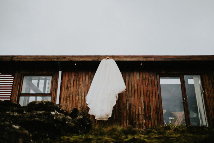 The wedding dress is hanging outside the apartment.