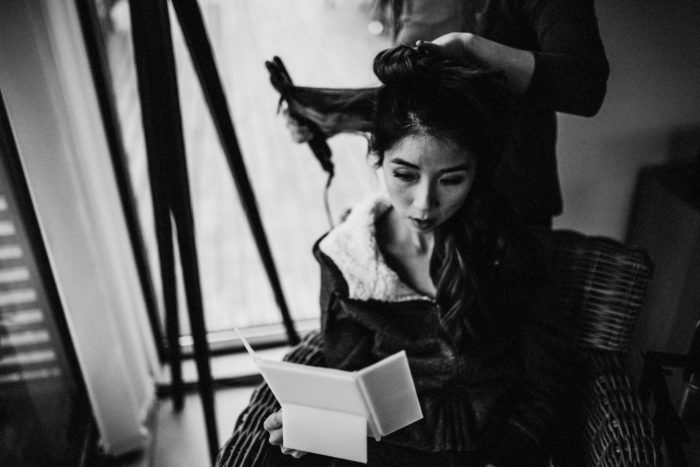 The bride is getting her hair done and is reading a letter.