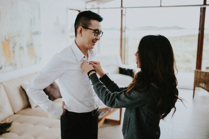 The groom is getting dressed by his bride.