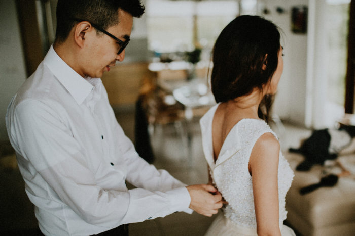 The groom is helping his bride to button up dress.