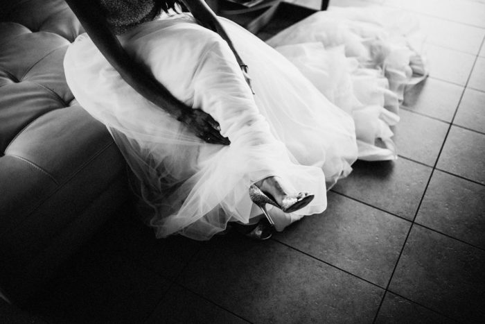 The bride is sitting on a sofa and wearing her wedding dress.