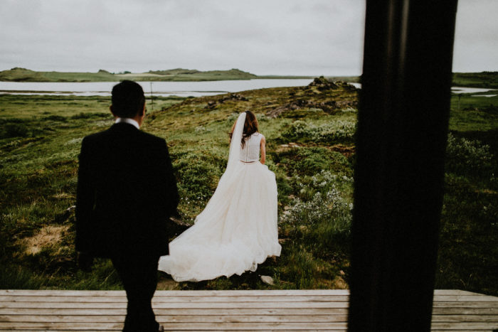 The wedding couple is leaving the terrace and walking into a meadow.
