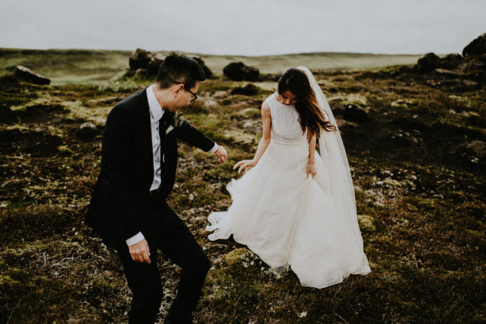 The wedding couple is walking across a rocky meadow.