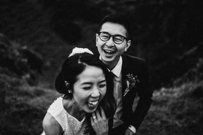 The wedding couple is laughing with each other.