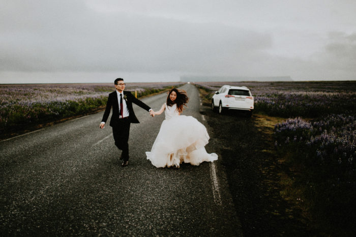 The wedding couple is holding hands and walking on a road.