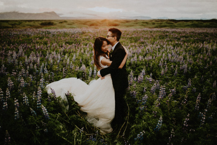 The wedding couple is standing in a field of lupines and is holding each other.