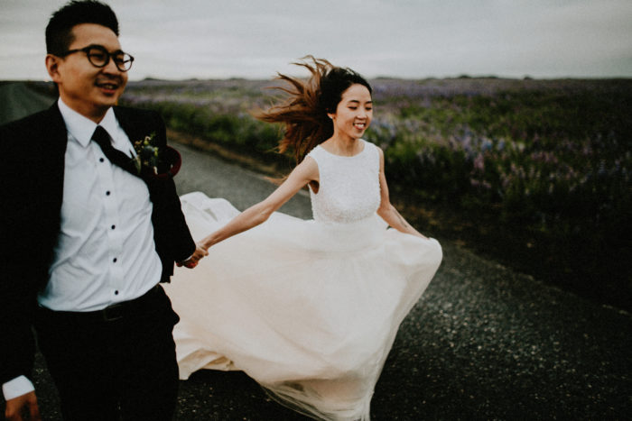 The wedding couple is running down a road.
