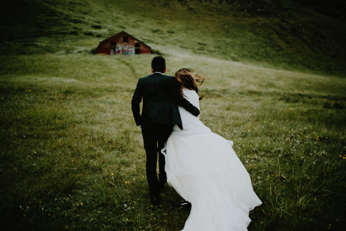 The wedding couple is walking up a hill towards an old building.