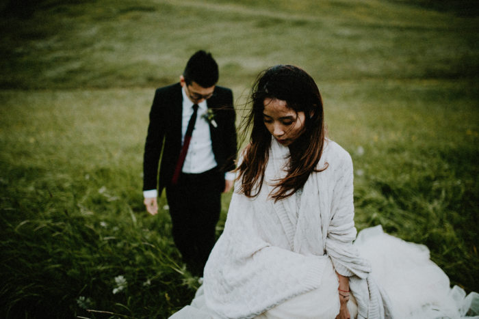 The wedding couple is walking through a meadow.