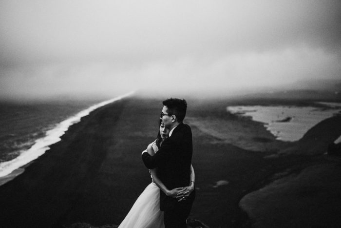 The wedding couple is standing on top of a mountain and looking towards the beach.
