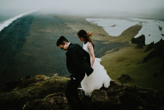 The wedding couple is walking up a mountain.