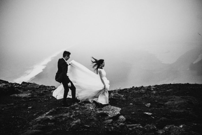 The wedding couple is walking through the rocky landscape and the groom is holding the brides wedding dress.