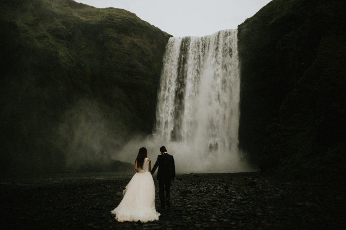 The wedding couple is walking towards a waterfall.