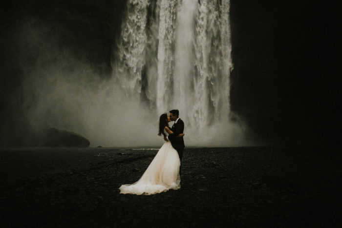 The wedding couple is kissing each other in front of a waterfall.