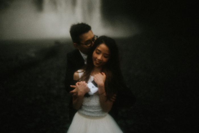 The wedding couple is holding each other and standing in front of a waterfall.