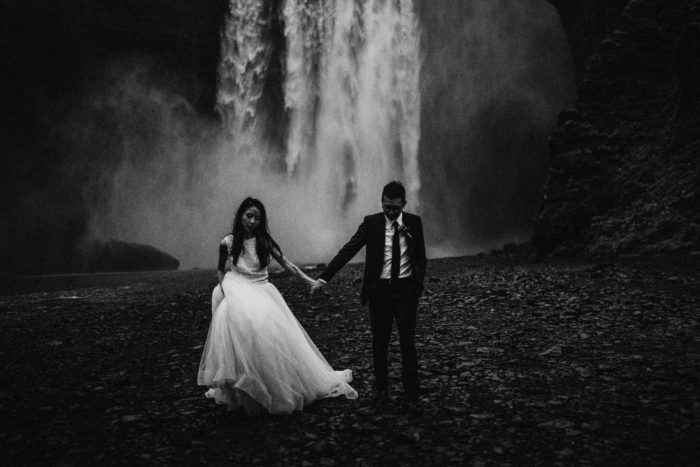 The wedding couple is holding hands in front of a waterfall.