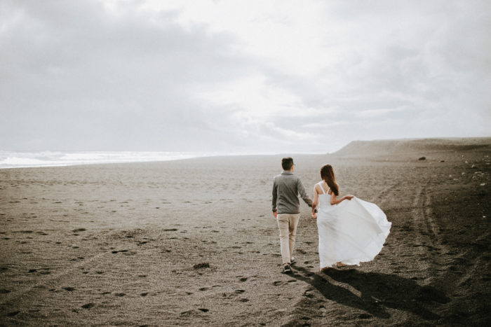 The wedding couple is walking along the beach.