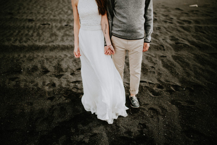 The wedding couple is holding hands and standing at the beach.