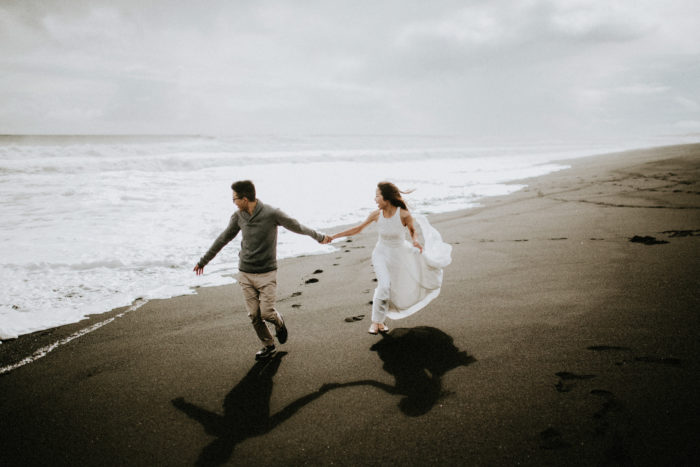 The wedding couple is running along the beach.