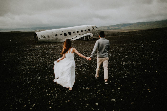 The wedding couple is walking towards an airplane wreck.
