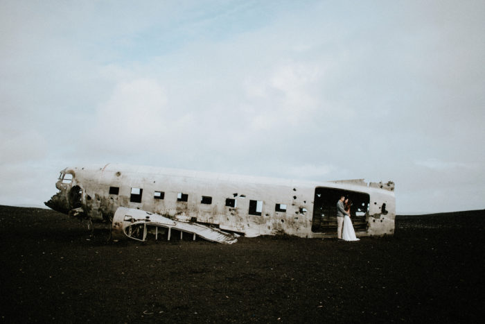 The wedding couple is holding each other at an airplane wreck.