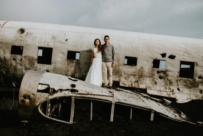 The wedding couple is standing on the wing of an airplane wreck.