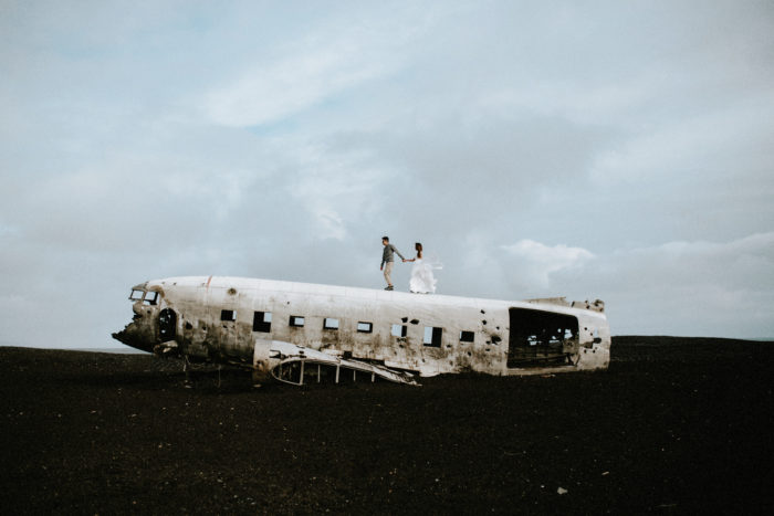 The wedding couple is walking on an airplane wreck.