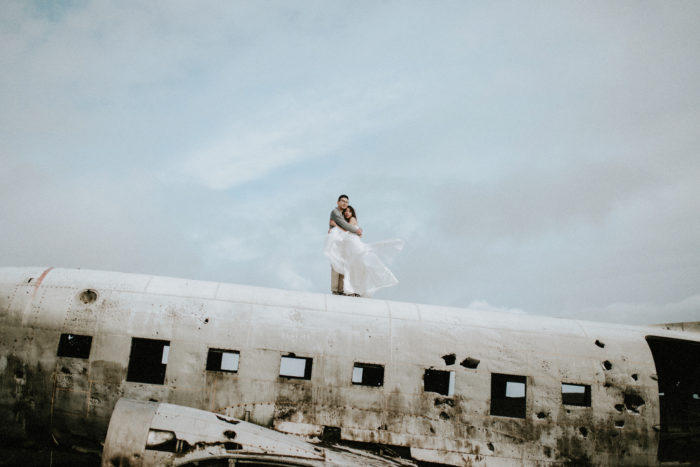 The wedding couple is holding each other on top of an airplane wreck.
