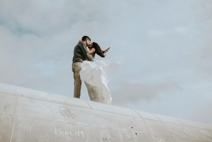 The wedding couple is kissing each other on top of an airplane wreck.