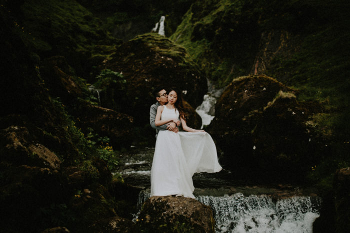 The wedding couple holding each other next to a small river and a small waterfall.