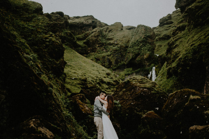 The wedding couple is kissing each other in front of rocky and a small waterfall.