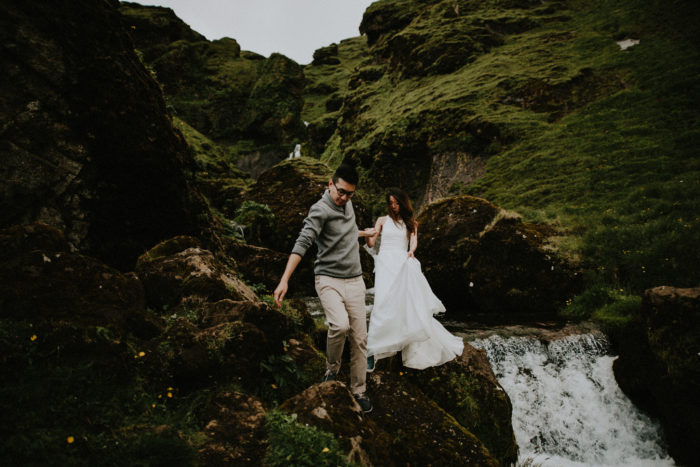 The wedding couple is leaving the waterfall location.