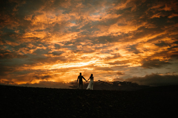 The wedding couple is walking along the beach in Iceland while the sun is setting.