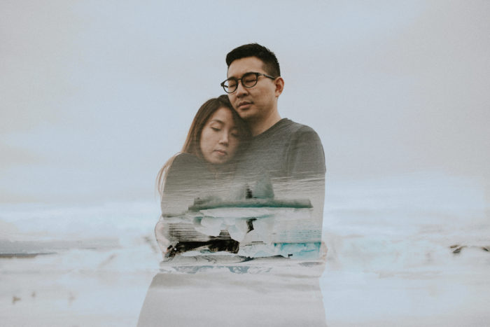 The wedding couple is holding each other and standing near the ocean.