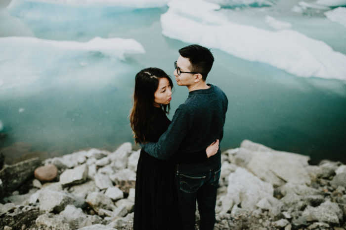 The wedding couple is standing next to the ocean, which is filled with ice blocks.