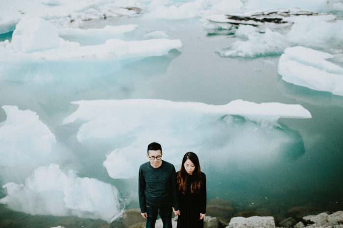 The wedding couple is standing next to the ocean filled with ice blocks.