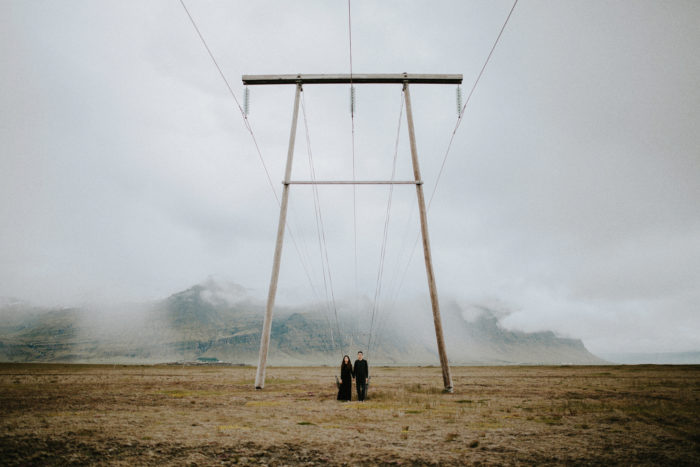 The wedding couple is standing under a power pole in a meadow.