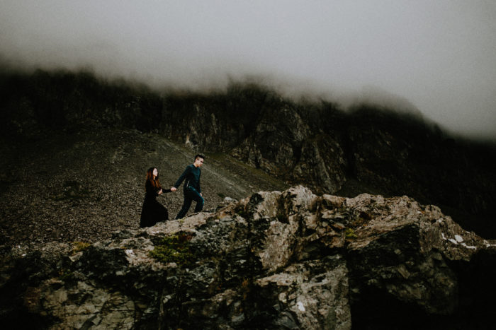 The wedding couple is walking up a mountain and is holding hands.