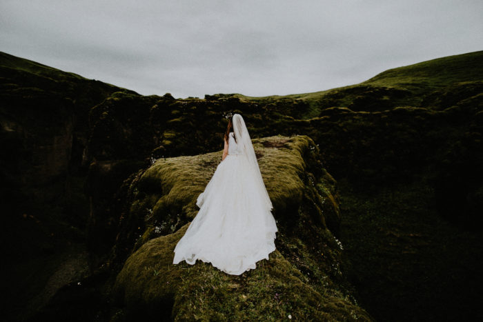 The bride is standing on a rocky part of the meadow next to a canyon.