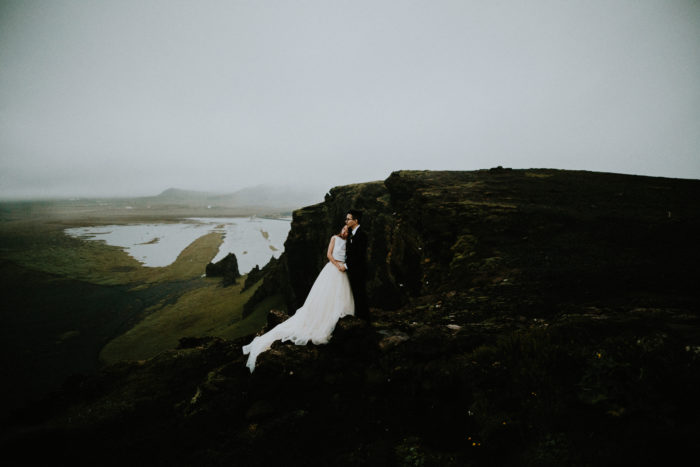 The wedding couple is standing on the mountain.