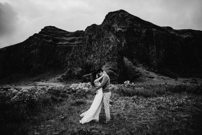 The wedding couple is holding each other in front of a mountain.