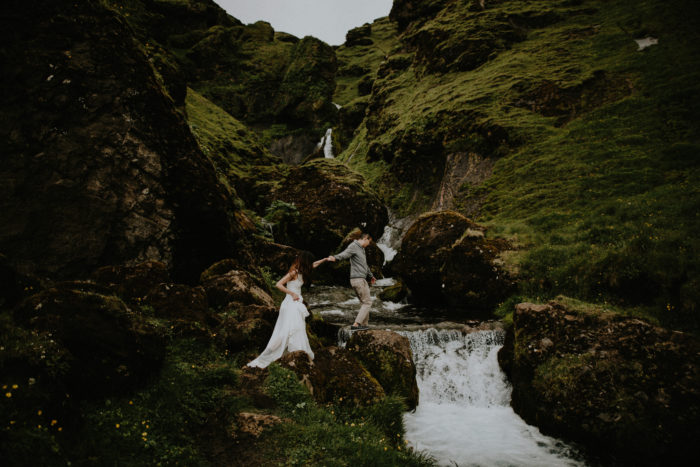 The wedding couple is walking along a small river towards a small waterfall.