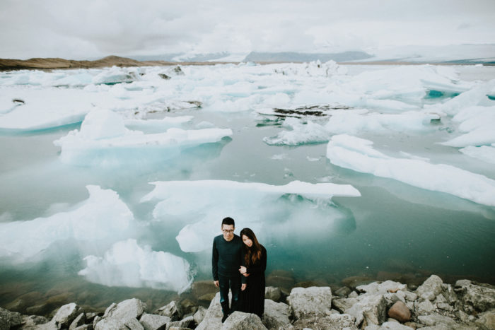 The wedding couple is standing on rocks right next to the ocean, which is filled with ice blocks.