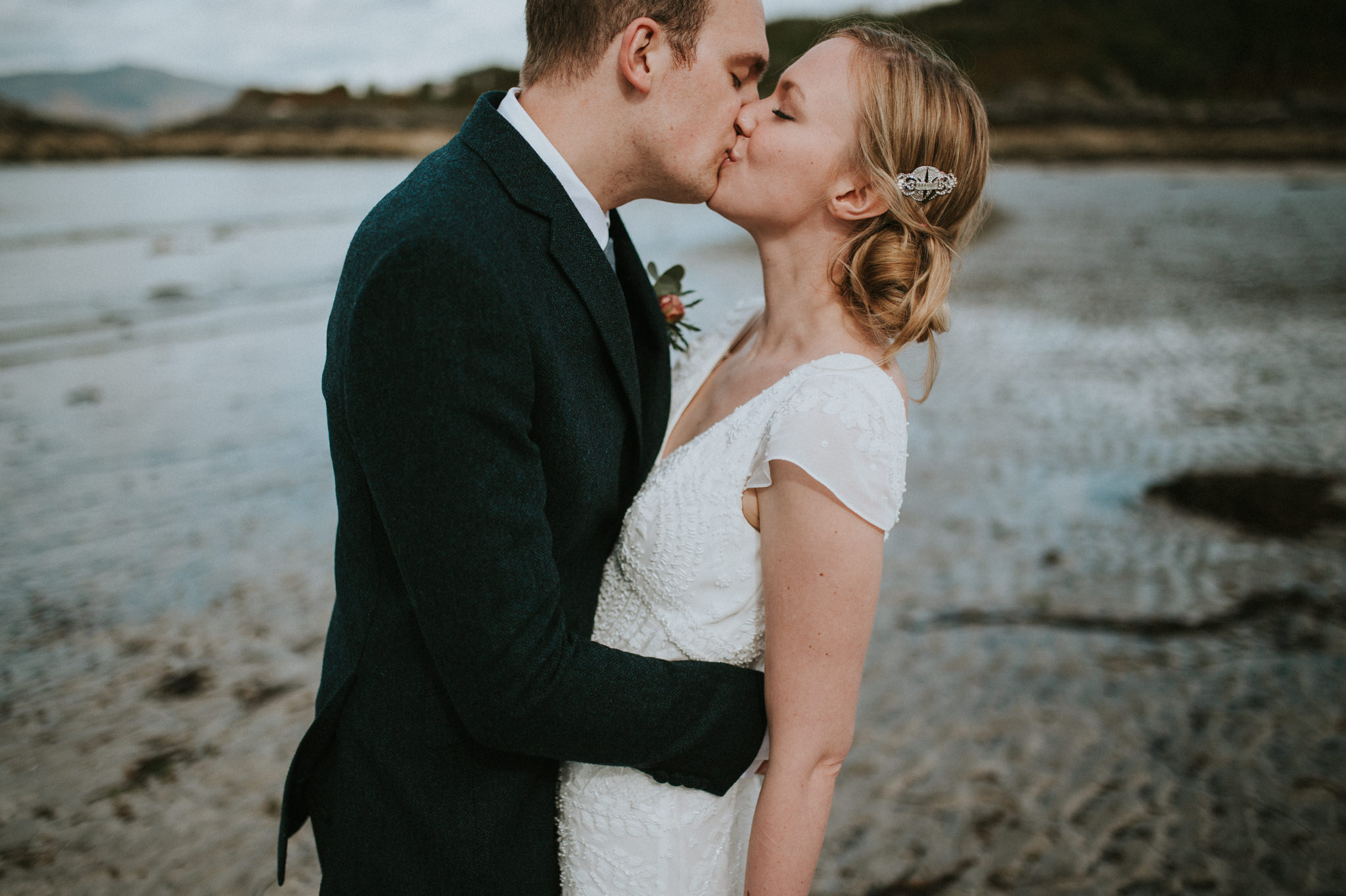 The wedding couple is kissing each other at the beach.