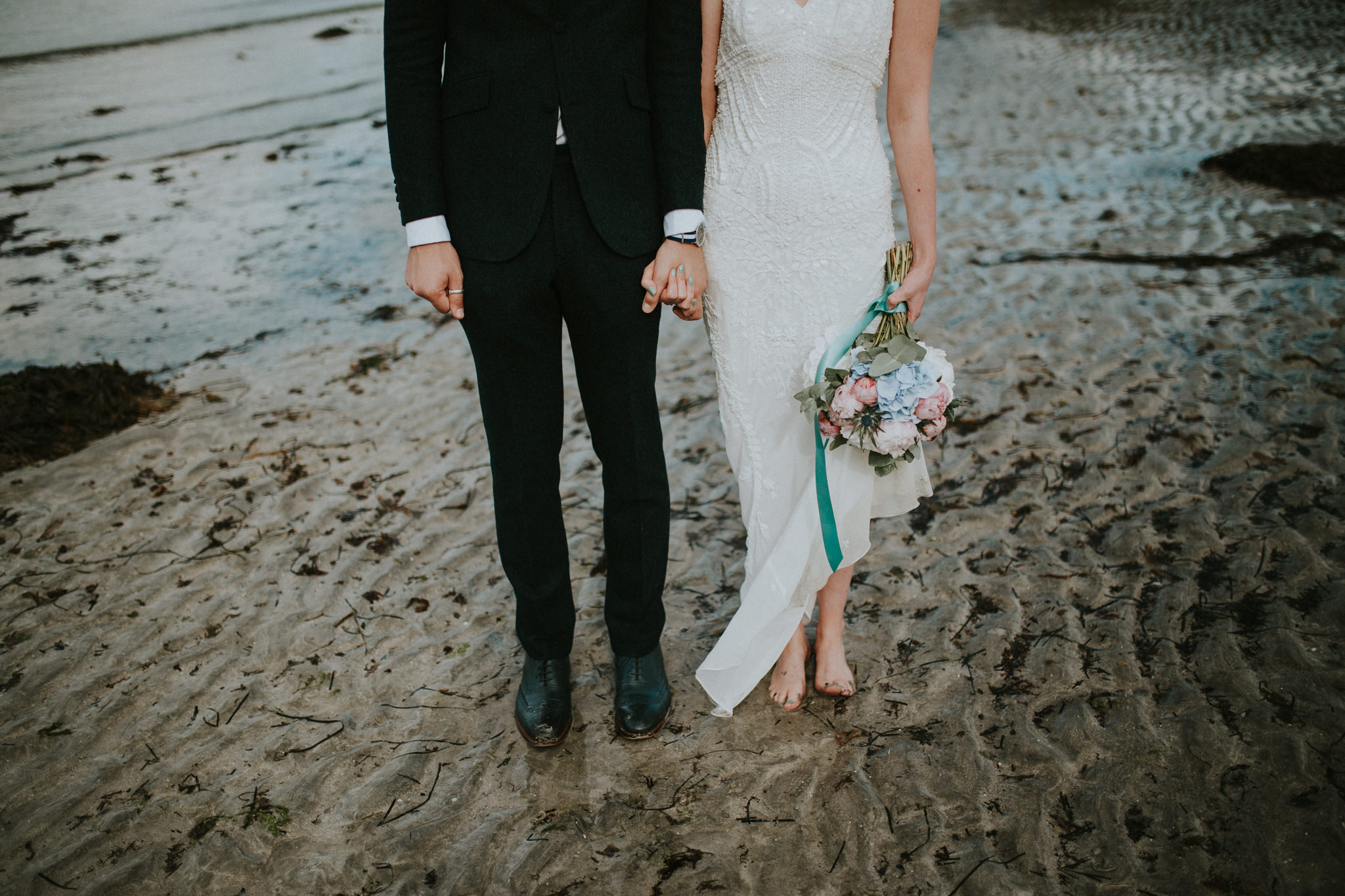 The wedding couple is standing at the beach.
