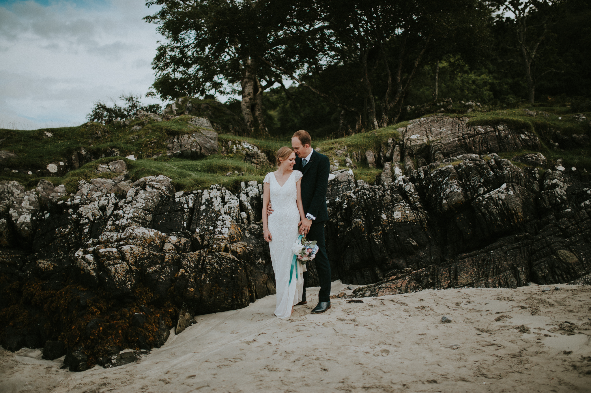 The wedding couple is standing at the beach next to some rocks and trees.