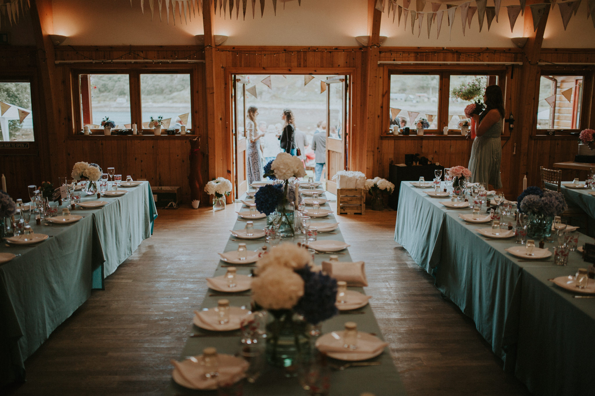 The wedding table is decorated with blue flowers and mint green table cloths.