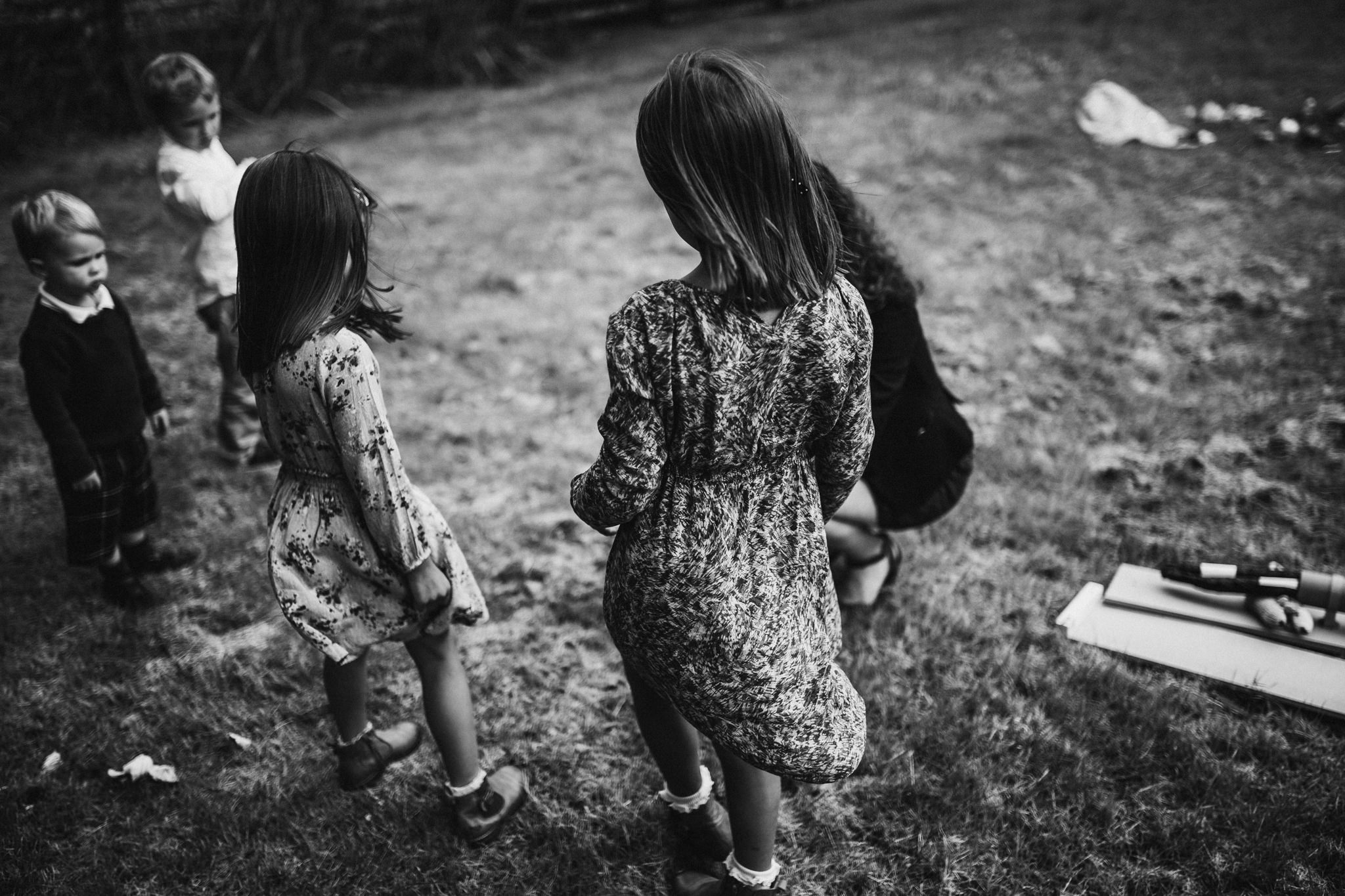 Little girls are walking on a meadow near the beach.