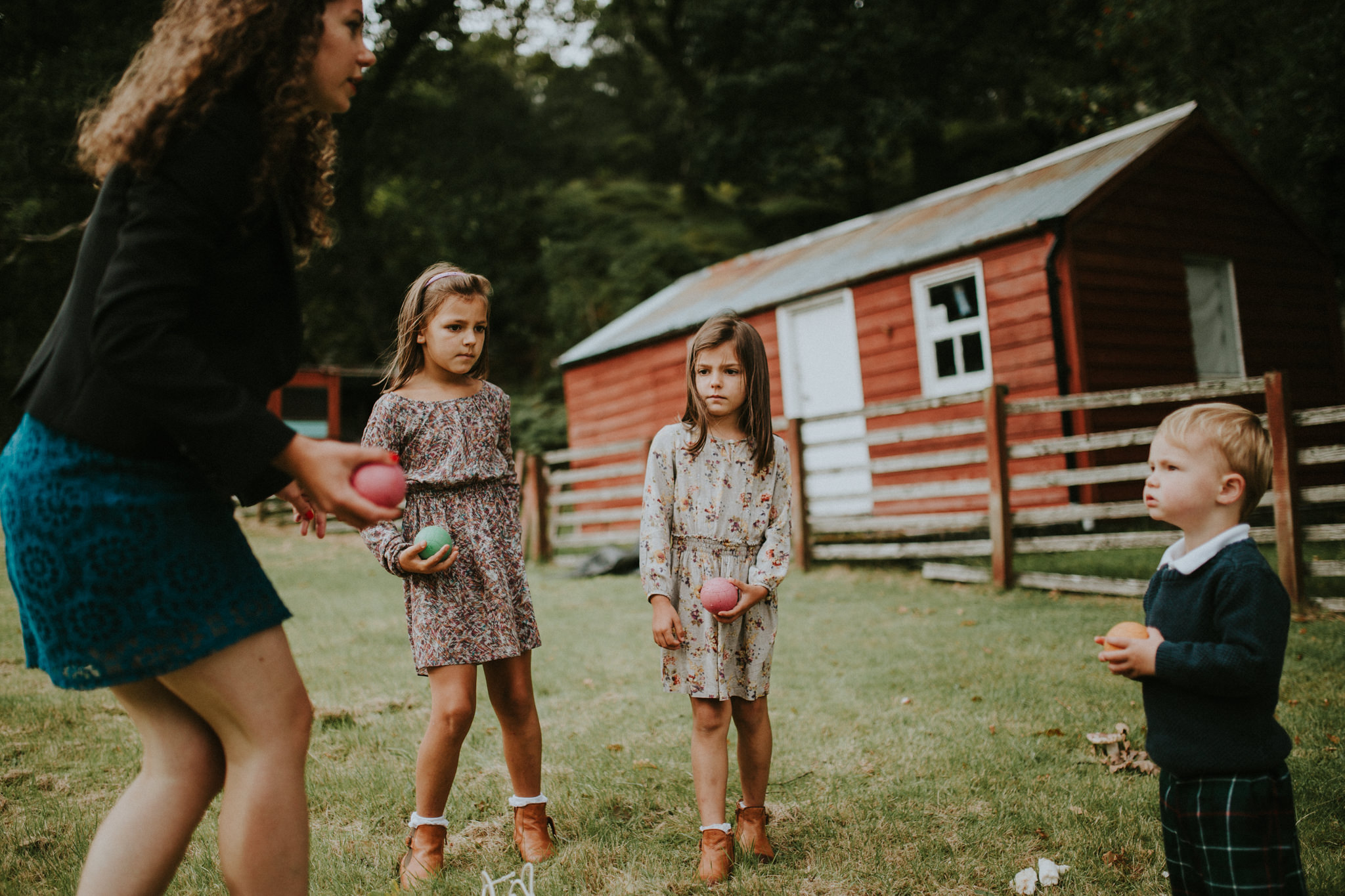 Girls are standing on a meadow in front of a barn.