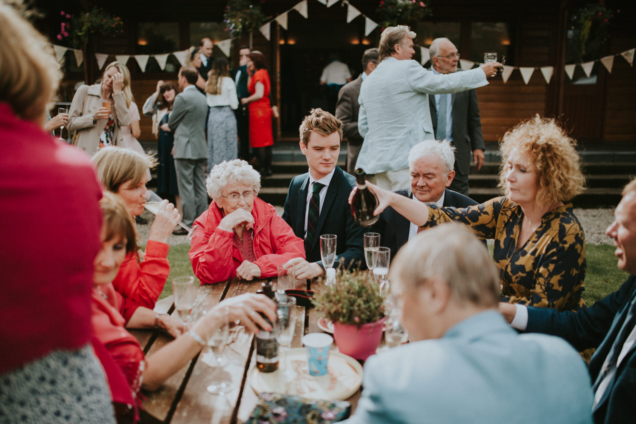 Wedding guests are sitting outside at a wooden table.